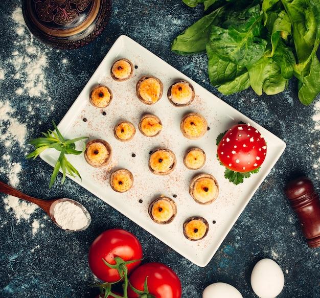 Bovenaanzicht van gegrilde champignons gevuld met gesmolten kaas