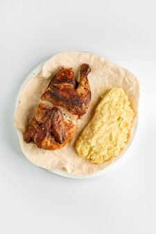 Bovenaanzicht van gegrilde kip half en aardappelpuree geserveerd op flatbread