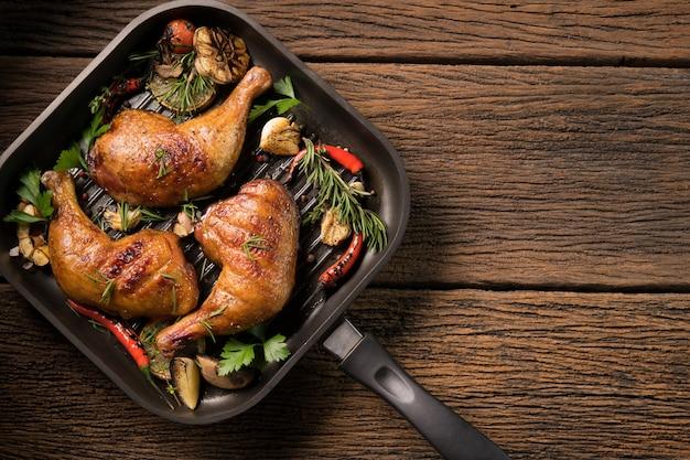 Bovenaanzicht van gegrilde kippendij met verschillende groenten op pan op oude houten achtergrond
