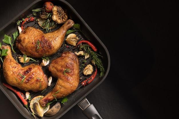 Bovenaanzicht van gegrilde kippendij met verschillende groenten op pan op zwarte achtergrond