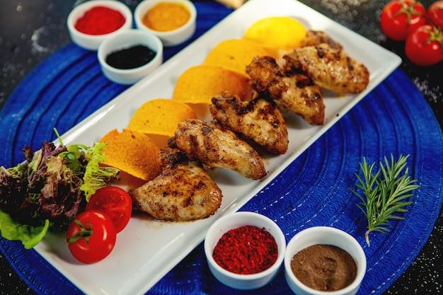 Bovenaanzicht van gegrilde kippenvleugeltjes geserveerd met gebakken aardappelen en verse salade