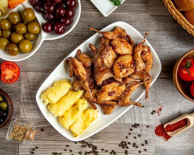 Bovenaanzicht van gegrilde kwartel met lula kebab van aardappelen geserveerd met augurken op tafel