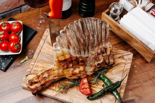 Bovenaanzicht van gegrilde ribben geserveerd met groenten op een houten bord