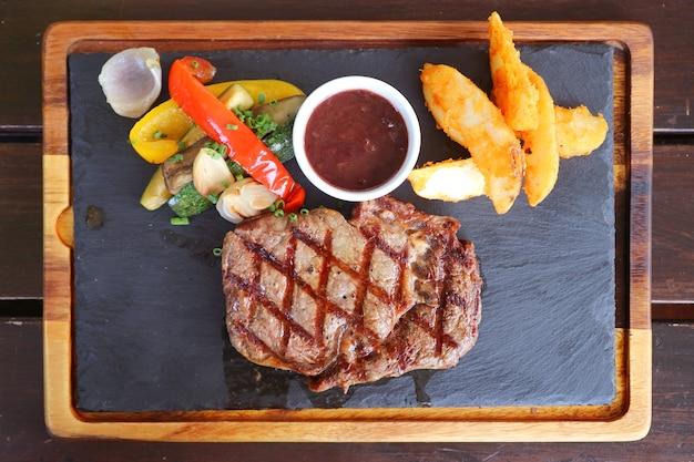 Bovenaanzicht van gegrilde ribeye steak met gebakken groenten geserveerd op hete stenen plaat
