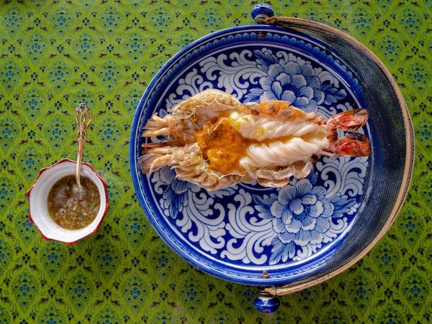 Bovenaanzicht van gegrilde riviergarnalen met pittige zeevruchtensaus op thaise traditionele stijl tafel. heerlijk thais eten.