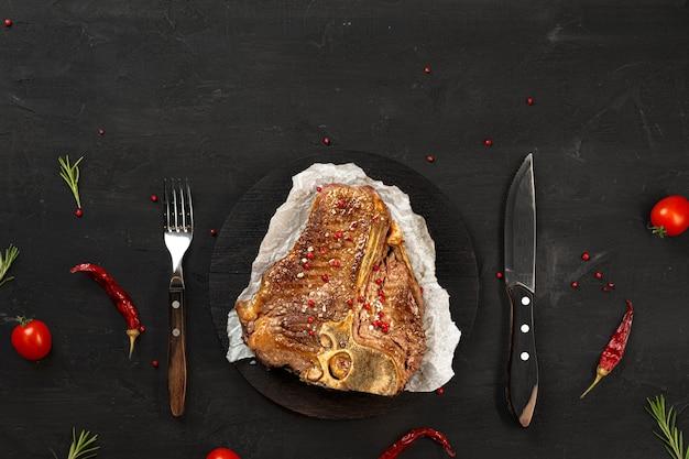 Bovenaanzicht van gegrilde t-bone steak met kruiden op zwarte tafel