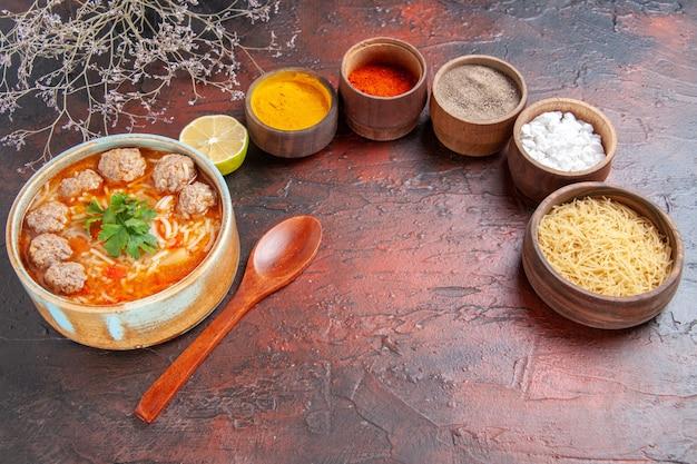 Bovenaanzicht van gehaktballensoep met noedels in een bruine kom, citroenlepel en verschillende kruiden op donkere tafel