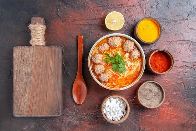 Bovenaanzicht van gehaktballensoep met noedels in een bruine kom, citroenlepel verschillende kruiden en snijplank op donkere tafel