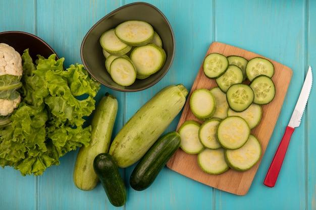 Bovenaanzicht van gehakte courgettes en komkommers op een houten keukenbord met mes met bloemkool en sla op een kom met hele komkommers en courgettes geïsoleerd op een blauwe houten ondergrond