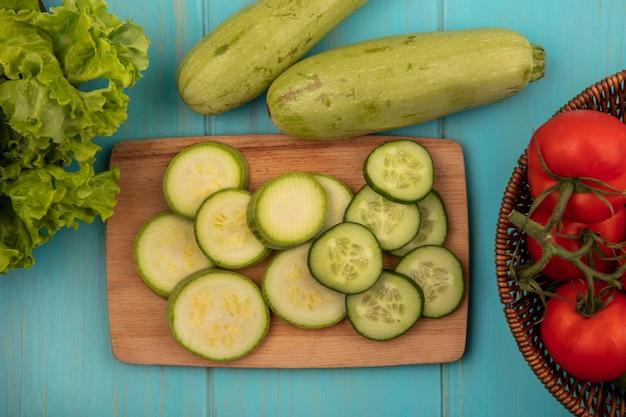 Bovenaanzicht van gehakte courgettes en komkommers op een houten keukenbord met tomaten op een emmer met sla en courgettes geïsoleerd op een blauwe houten muur