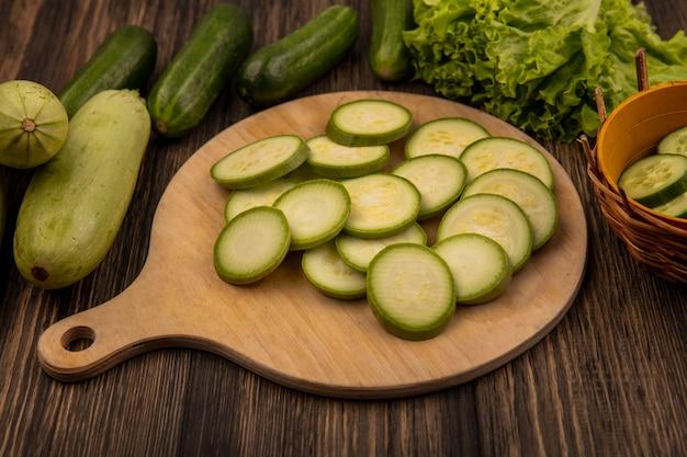 Bovenaanzicht van gehakte courgettes geïsoleerd op een houten keukenbord met komkommers en sla geïsoleerd op een houten achtergrond