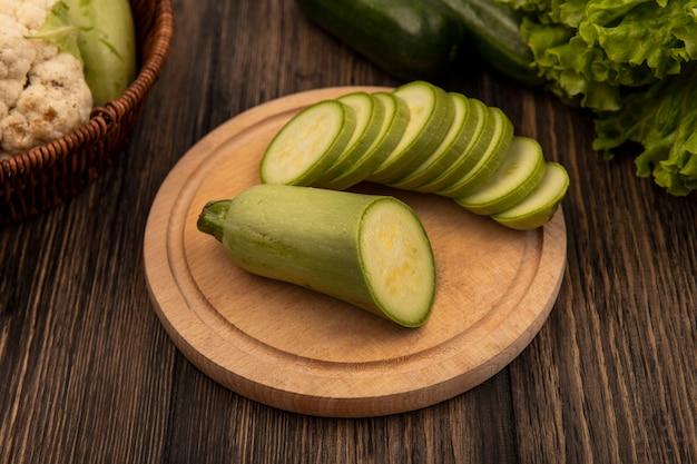 Bovenaanzicht van gehakte courgettes op een houten keukenbord met groenten zoals courgettes en bloemkool op een emmer met sla en komkommers geïsoleerd op een houten muur