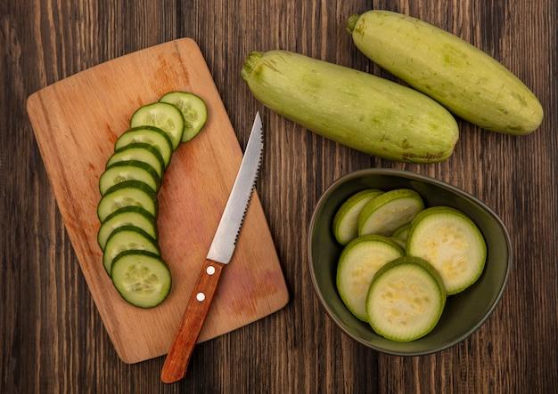 Bovenaanzicht van gehakte courgettes op een kom met gehakte komkommers op een houten keukenplank met mes met courgettes geïsoleerd op een houten muur