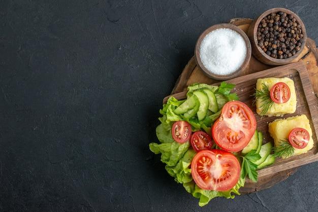 Bovenaanzicht van gehakte en hele verse groenten kaas op snijplank en kruiden aan de linkerkant op zwarte ondergrond