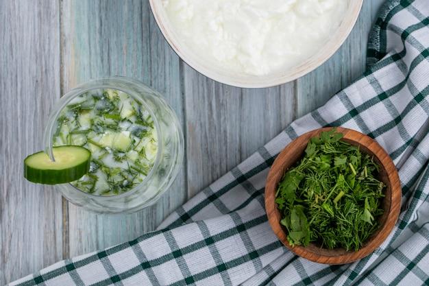 Bovenaanzicht van gehakte greens in een kom op een witte geruite handdoek met acroshka en yoghurt op een grijze ondergrond