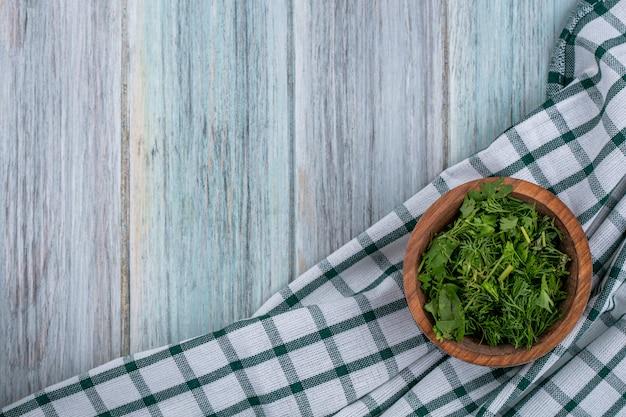 Bovenaanzicht van gehakte greens in een kom op een witte geruite handdoek op een grijze ondergrond