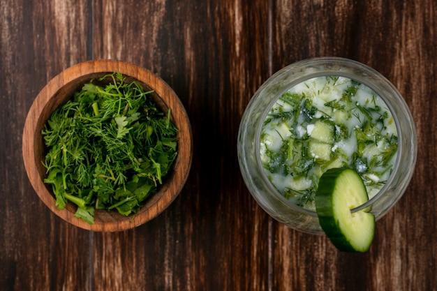 Bovenaanzicht van gehakte greens met okroshka en komkommer op een houten oppervlak