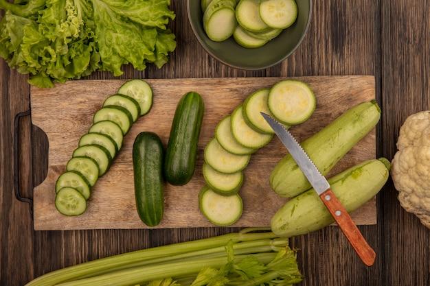 Bovenaanzicht van gehakte komkommers en courgettes geïsoleerd op een houten keukenplank met mes met sla selderij en bloemkool geïsoleerd op een houten muur