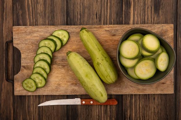 Bovenaanzicht van gehakte komkommers en courgettes geïsoleerd op een houten keukenplank met mes op een houten achtergrond