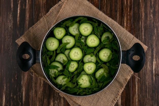 Bovenaanzicht van gehakte komkommers in een pan met munt op een houten oppervlak