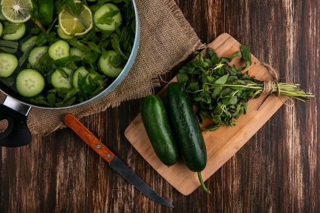 Bovenaanzicht van gehakte komkommers met munt in een pan met een snijplank en mes op een houten oppervlak