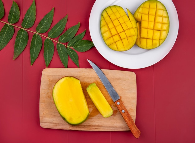 Bovenaanzicht van gehakte mango met mes op houten keukenbord met gesneden mango in een witte plaat met blad op rood