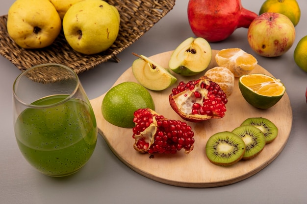 Bovenaanzicht van gehakte plakjes kiwi met plakjes appel, mandarijn en granaatappel op een houten keukenbord met kweeperen op een rieten dienblad met vers vruchtensap op een grijze muur