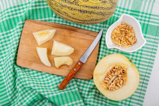 Bovenaanzicht van gehakte plakjes meloen op houten keukenbord met mes met zaden op witte kom op geel geruit tafelkleed