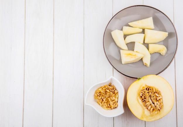 Bovenaanzicht van gehakte plakjes meloen op plaat met zaden op kom op wit met kopie ruimte
