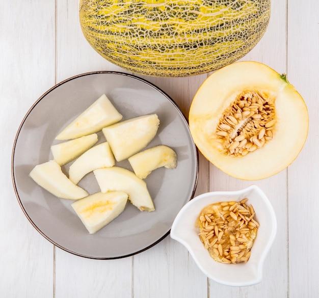 Bovenaanzicht van gehakte plakjes meloen op plaat met zaden op witte kom op wit
