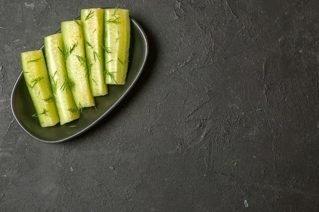 Bovenaanzicht van gehakte verse komkommer geserveerd met groen op een zwarte plaat op donkere muur