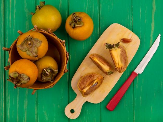 Bovenaanzicht van gehalveerde kaki fruit op een houten keukenplank met mes met kaki fruit op een emmer op een groene houten tafel
