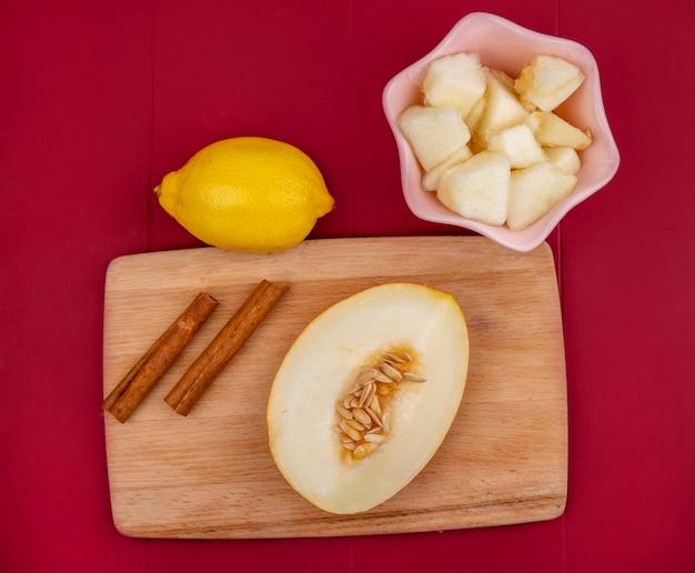 Bovenaanzicht van gehalveerde meloen op een houten keukenbord met kaneelstokjes met citroen met plakjes meloen op een roze kom op rode ondergrond