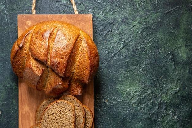 Bovenaanzicht van geheel en gesneden zwart brood op bruine houten snijplank aan de rechterkant op donkere kleuren achtergrond