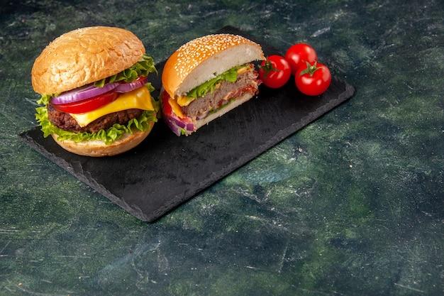 Bovenaanzicht van geheel gesneden verschillende smakelijke sandwiches en tomaten met stengel op zwarte lade bovenop op donkere mix kleur oppervlak