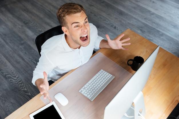 Bovenaanzicht van gekke jonge zakenman die met computer werkt en schreeuwt