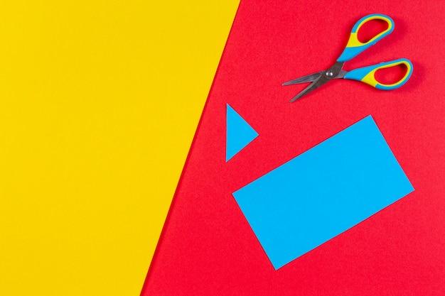 Bovenaanzicht van gekleurd papier met een kleurrijke schaar. kinderkunst en ambachtelijke papieren stoffen achtergrond