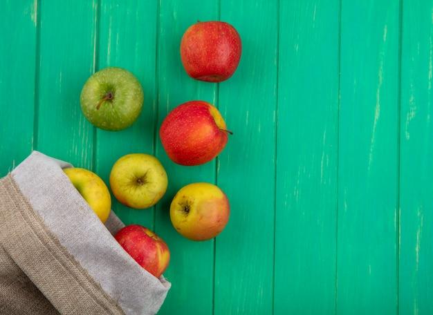 Bovenaanzicht van gekleurde appels in een jutezak op een groen oppervlak