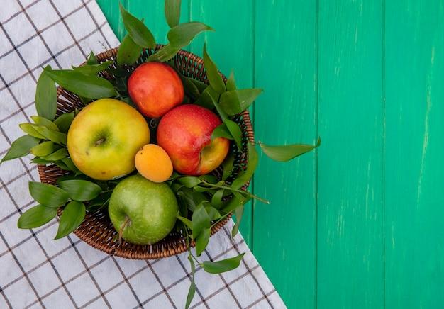 Bovenaanzicht van gekleurde appels in een mand met bladtakken met een wit geruite handdoek op een groen oppervlak