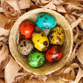 Bovenaanzicht van gekleurde eieren voor pasen in de mand