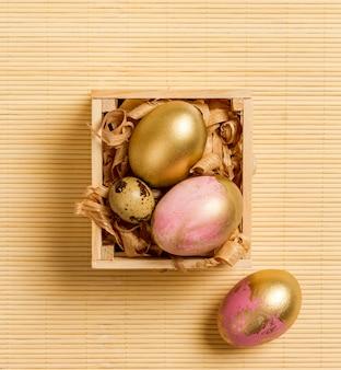 Bovenaanzicht van gekleurde eieren voor pasen in houten kist