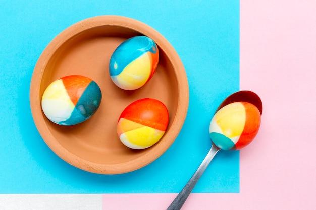 Bovenaanzicht van gekleurde eieren voor pasen op plaat met lepel