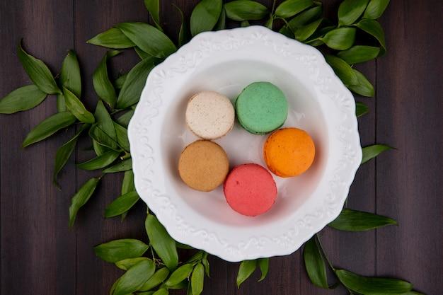 Bovenaanzicht van gekleurde macarons in een plaat met bladtakken op een houten oppervlak
