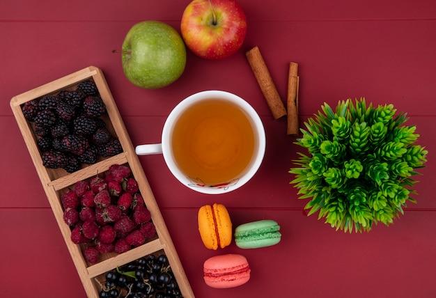 Bovenaanzicht van gekleurde macarons met een kopje thee frambozen, bramen, zwarte bessen en appels op een rode ondergrond