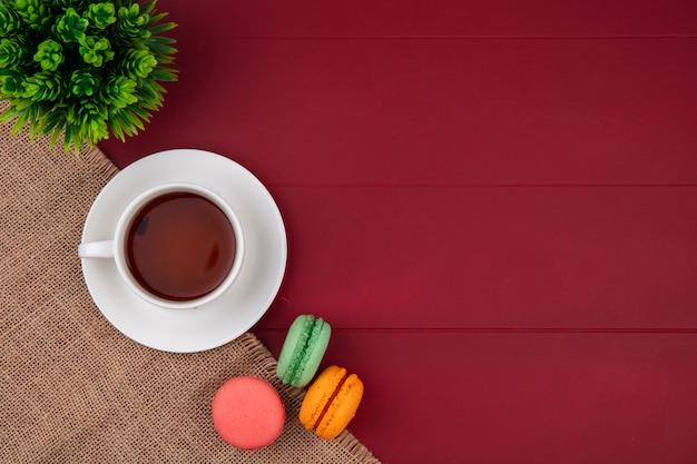 Bovenaanzicht van gekleurde macarons met een kopje thee op een beige servet op een rood oppervlak