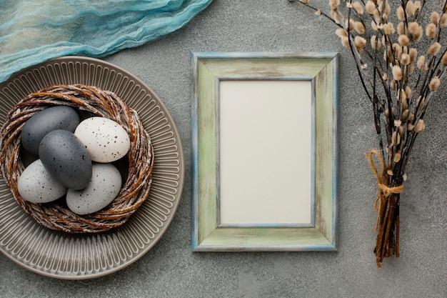 Bovenaanzicht van gekleurde paaseieren in mand met frame en twijgen