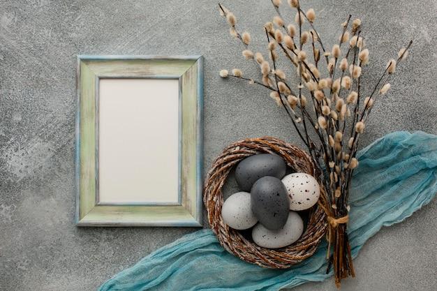 Bovenaanzicht van gekleurde paaseieren in mand met twijgen en frame