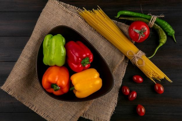 Bovenaanzicht van gekleurde paprika in een kom met rauwe spaghetti chili pepers en tomaten op een houten oppervlak