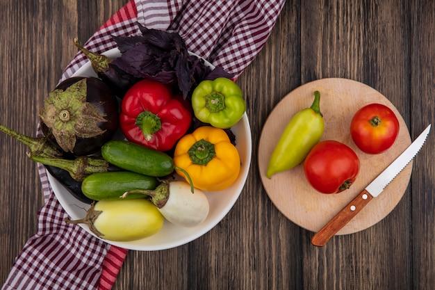 Bovenaanzicht van gekleurde paprika met komkommers, aubergine en baslik op een bord met tomaten en een mes op een snijplank op een houten achtergrond