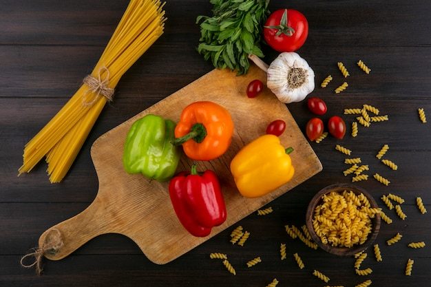 Bovenaanzicht van gekleurde paprika op een snijplank met knoflook gewassen en rauwe spaghetti op een houten oppervlak